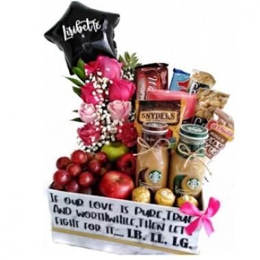 Cesta de snacks y flores en rosa