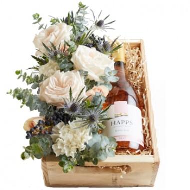 Caja con vino rosa y flores