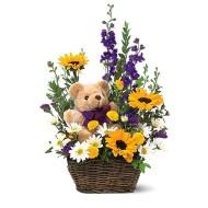 Canasta con flores primaverales y oso de peluche
